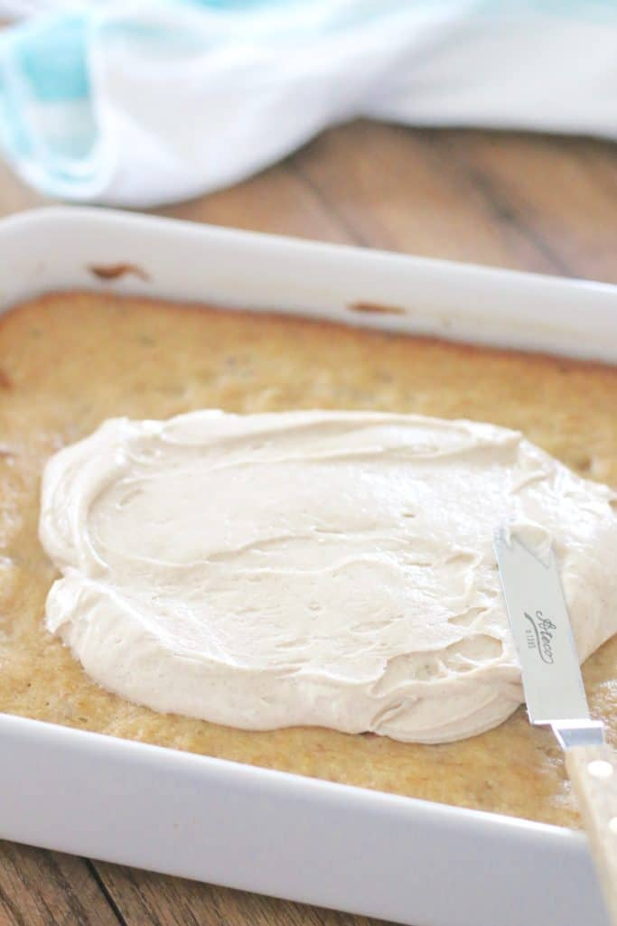 Homemade Cinnamon Cream Cheese Frosting spread on cooled Hummingbird Cake with offset spatula