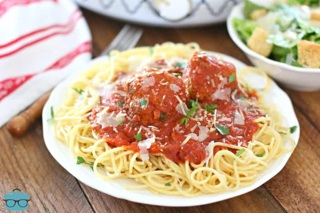 Spaghetti and meatballs served with a Caesar salad and a slow cooker in the background