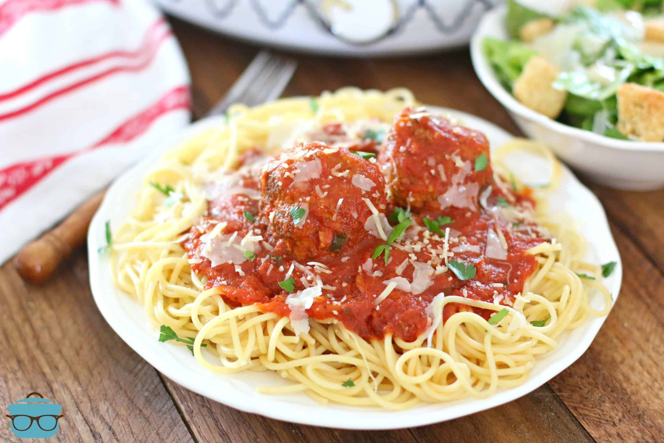 plate of spaghetti and marinara sauce with meatballs on a white circle plate