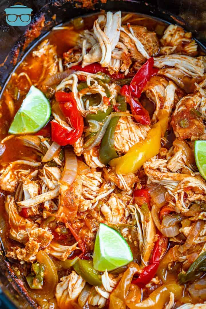 oval crock pot filled with cooked chicken fajita mixture with three lime wedges.