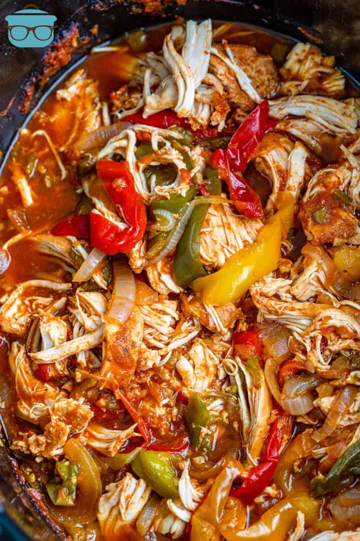 fully cooked chicken fajita mixture in oval black crock pot.
