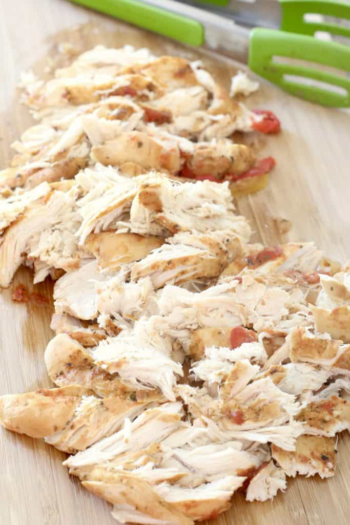 cooked chicken that has been shredded with a fork on a cutting board