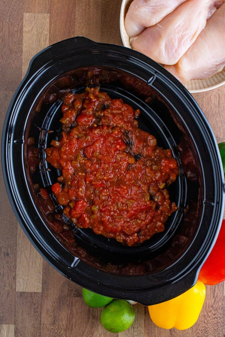 a layer of salsa shown in the bottom of a black oval slow cooker.