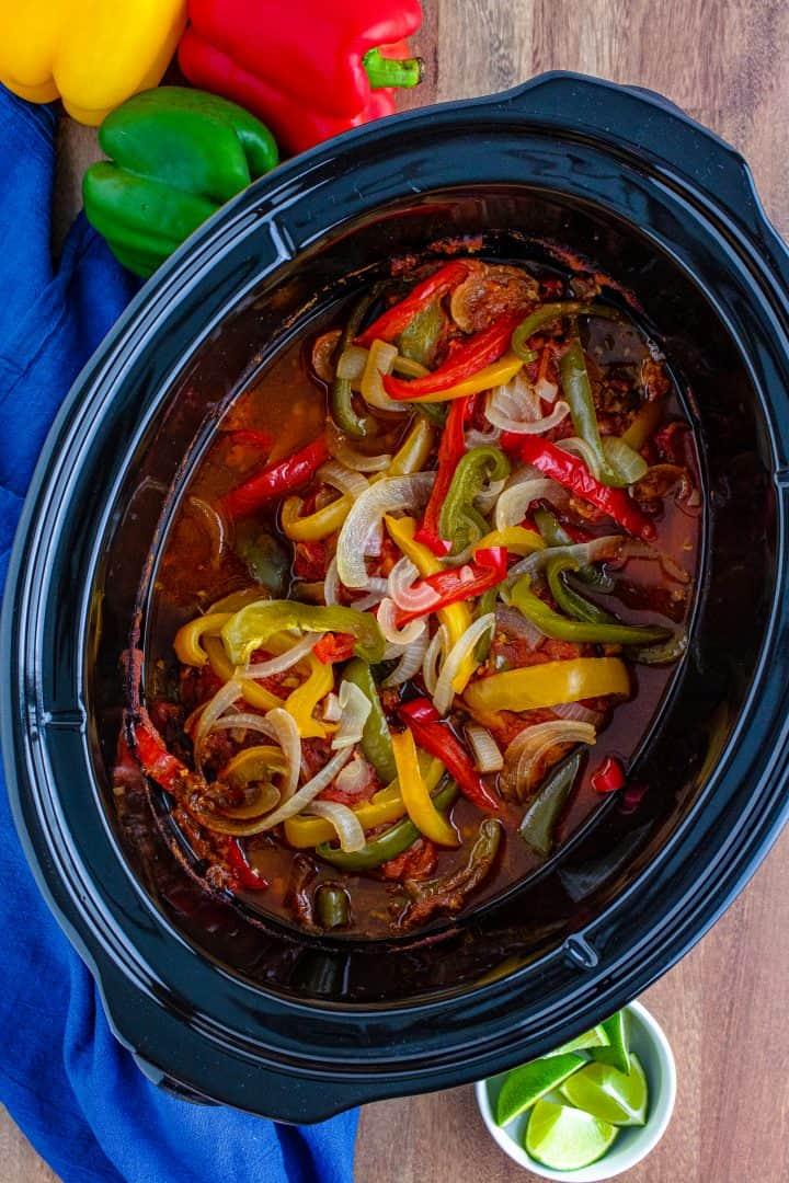 fully cooked chicken fajita filling show in oval crock pot.