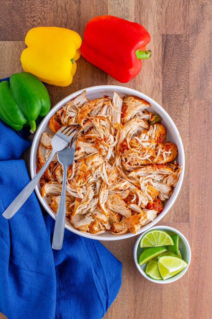 shredded cooked chicken breasts in a white bowl with two forks.