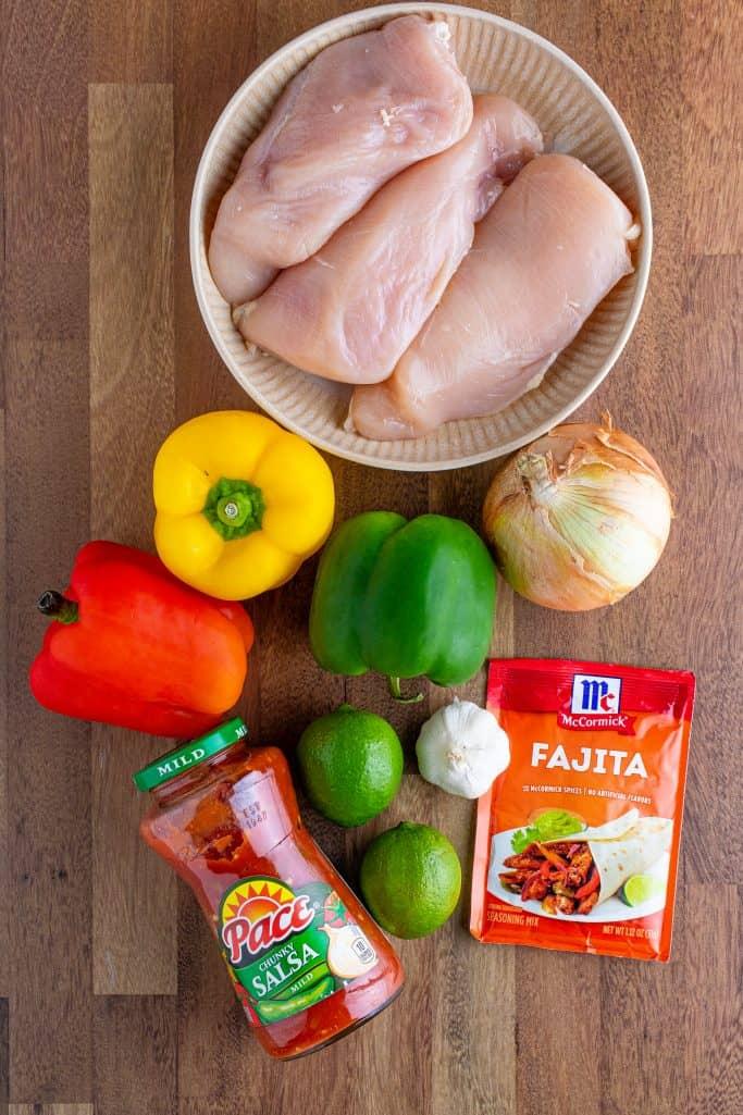 Ingredients needed to make chicken fajitas: red, yellow, green bell peppers, onion, garlic, salsa, boneless, skinless chicken breasts, fajita seasoning, fresh lime juice
