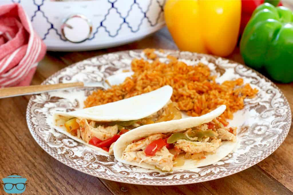 chicken fajita meat shown in flour tortillas with red rice on the side