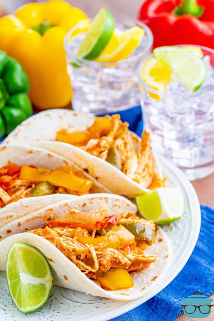 there flour tortillas filled with chicken fajita mixture on a white plate with three bell peppers in the background
