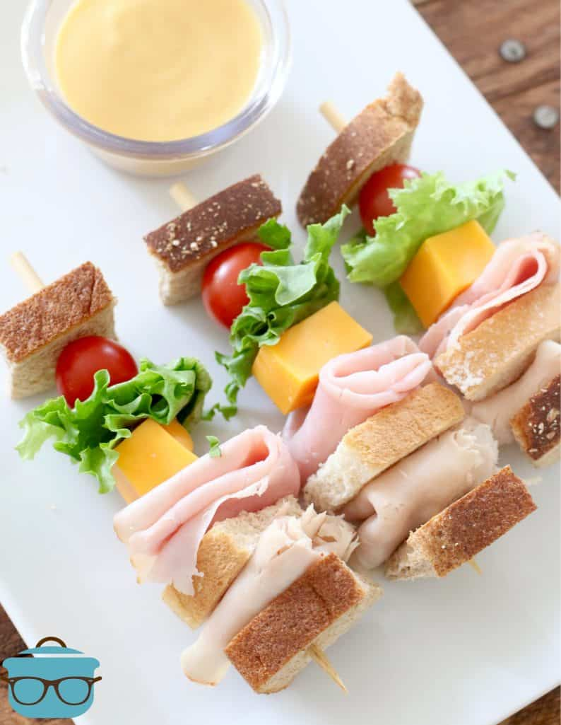 three club sandwiches on a stick shown on a white rectangle plate with a small bowl of honey mustard on the side