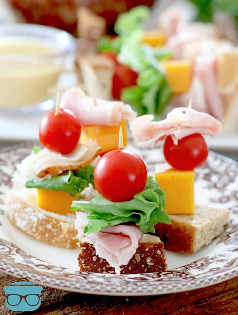 small stacked club sandwiches on toothpick shown with three on a plate