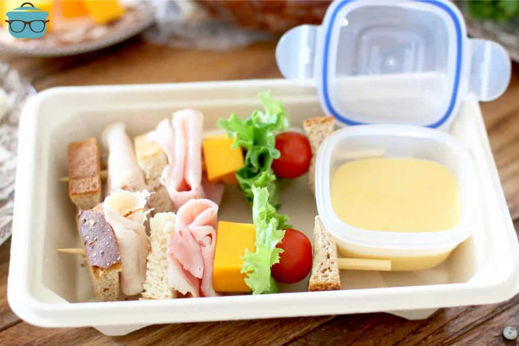 two club sandwiches on a stick shown in a rectangle lunch container