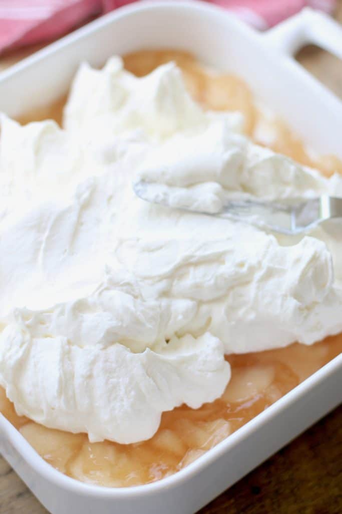 sweetened whipped cream cheese layer spread on top of apple pie filling layer
