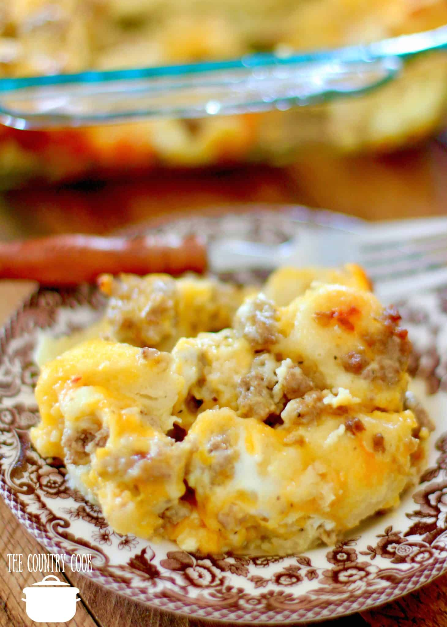 Easy Sausage Egg and Cheese Biscuit Casserole recipe. A serving shown on a brown and white small Spode plate.