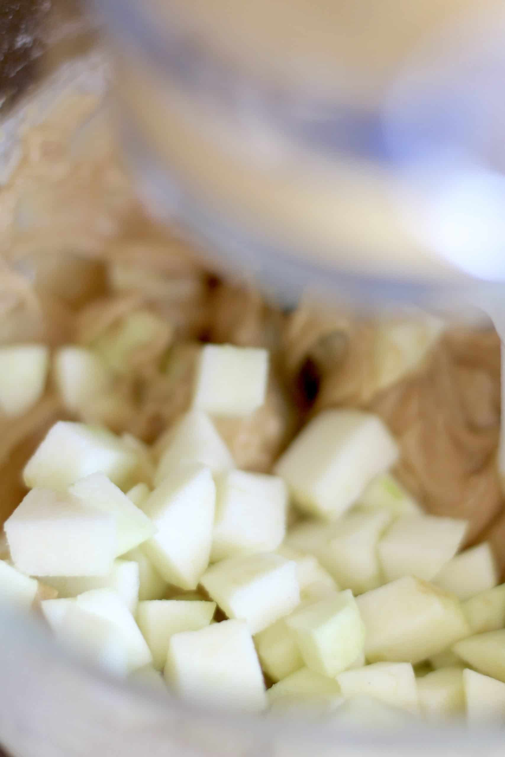chopped Granny Smith added to brown sugar batter in a clear bowl.