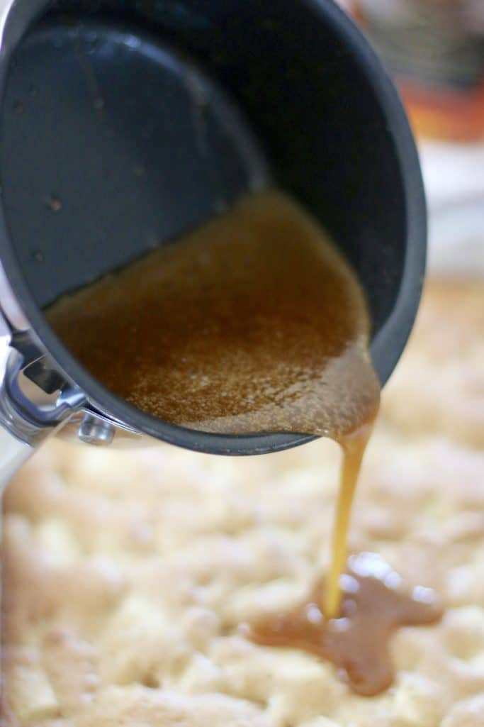 pouring brown sugar glaze over apple blondies
