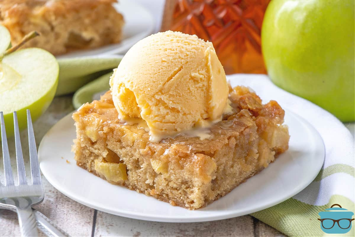 slice of glazed apple maple blondie on a white plate and topped with a scoop of vanilla ice cream.