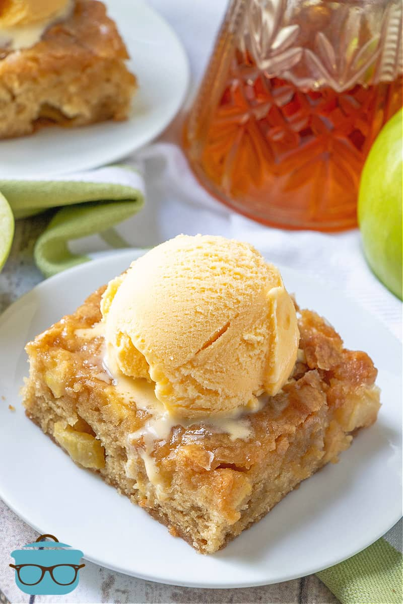 Maple Glazed Apple Blondies, slice shown on a white plate, topped with vanilla ice cream, maple syrup pictured in the background.