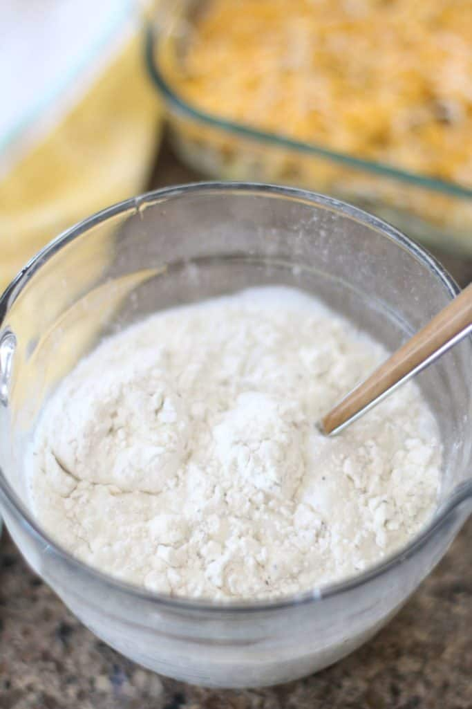 packet white creamy gravy mix with water stirred together in a Pampered Chef measuring cup