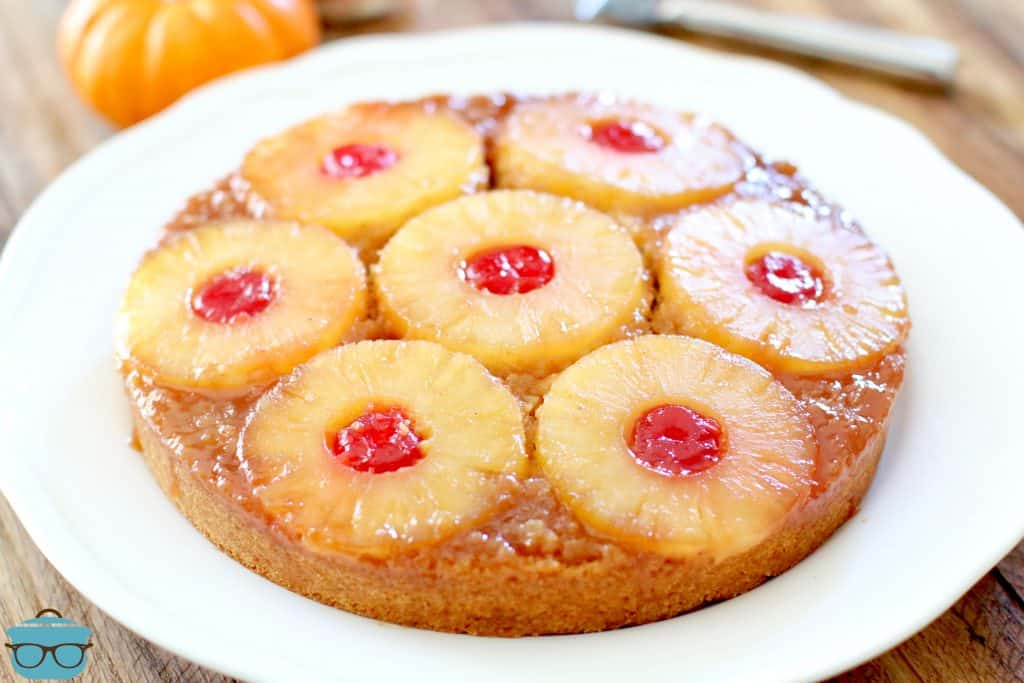 pineapple upside down cake shown on a round white plate on a wood surface