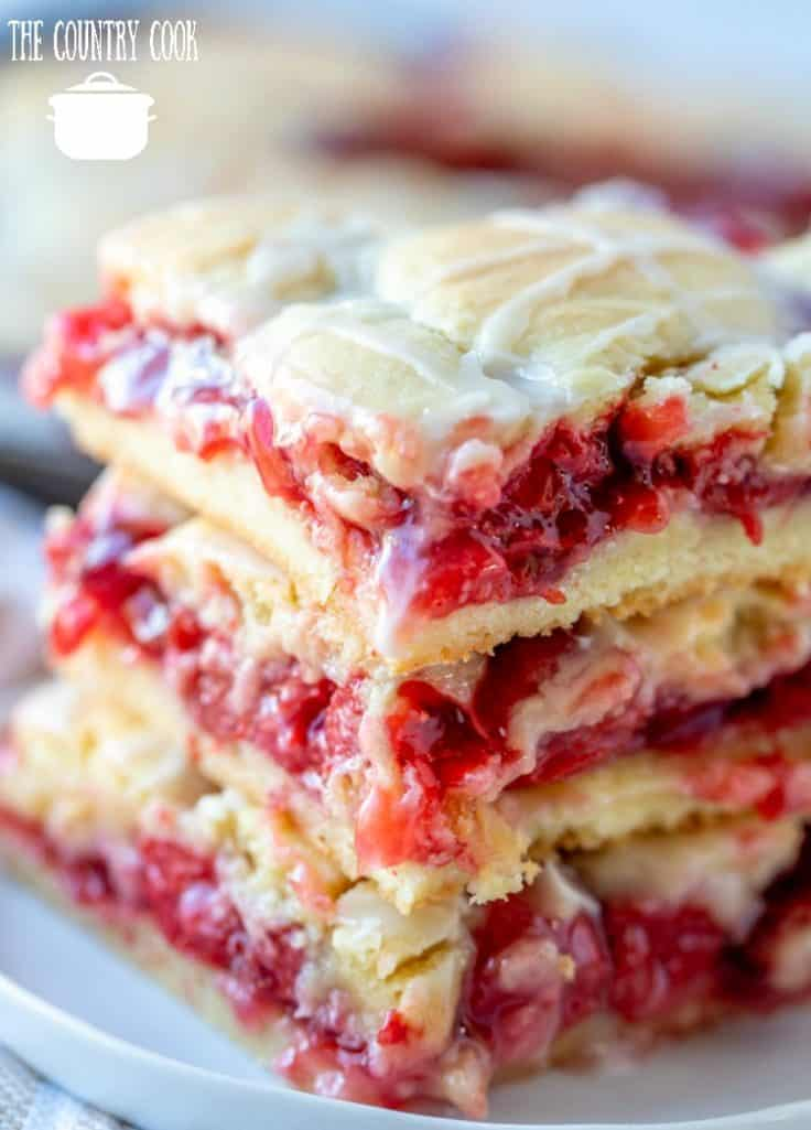 cherry pie bars, shown close up, three cherry bars stacked on top of each other on a white plate
