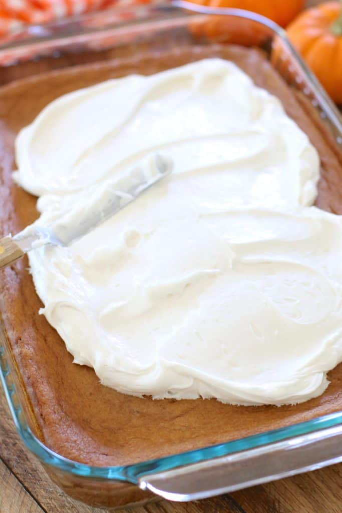 spreading white premade frosting on cooled pumpkin pie cake with an offset spatula