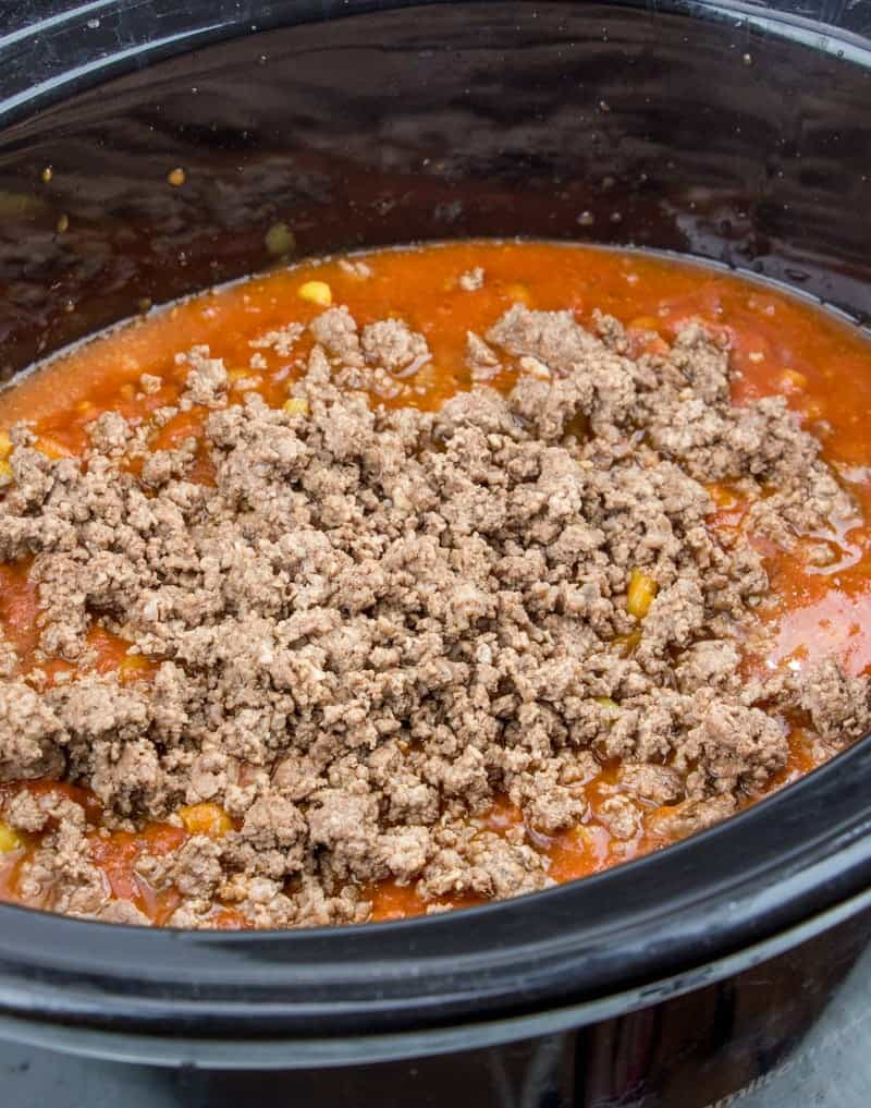 cooked ground beef added to crock pot along with cavatappi noodles and spaghetti sauce