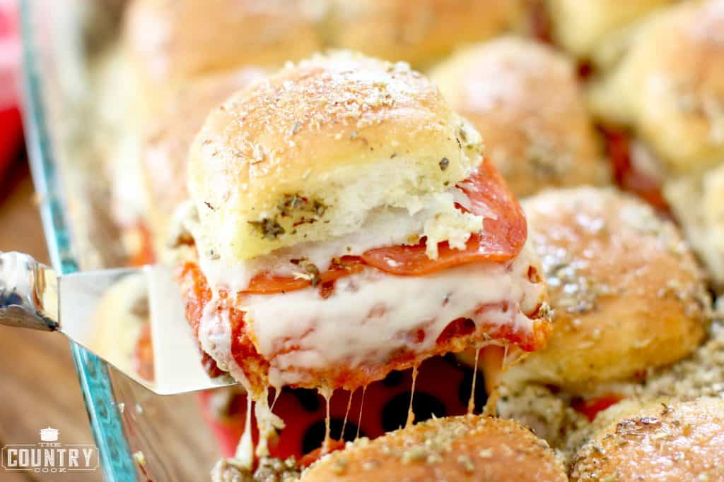 shown: one pizza slider on a small serving spatula removing from the tray of cooked pizza pull apart sliders