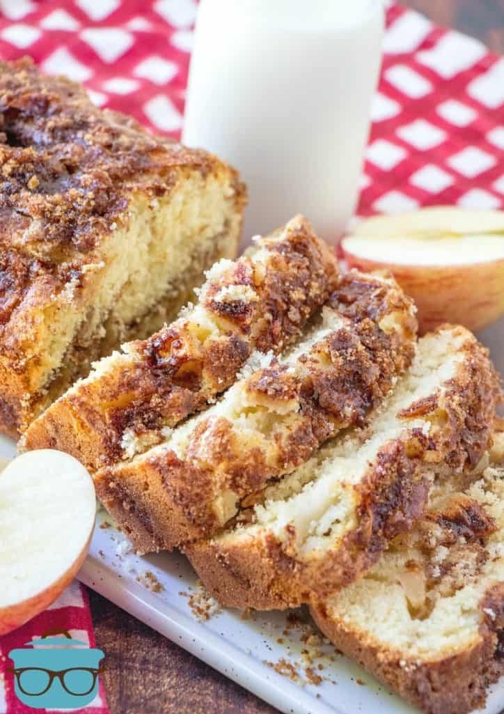 sliced Homemade Apple Pie Bread on a long with tray with milk and sliced apples pictured in the backgrund