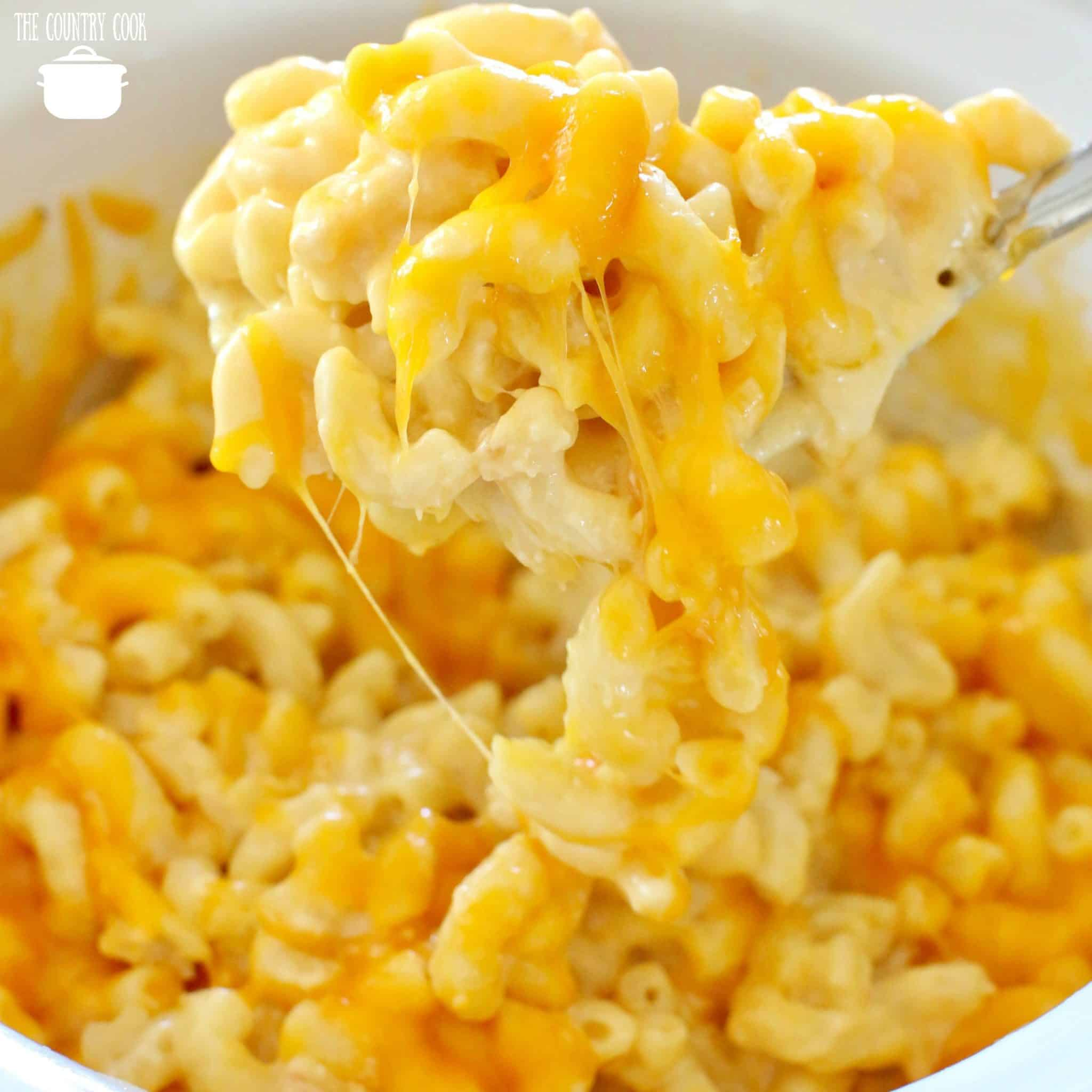 Crock Pot Macaroni and Cheese recipe from The Country Cook. Large spoon scooping out some creamy macaroni and cheese from a crock pot.