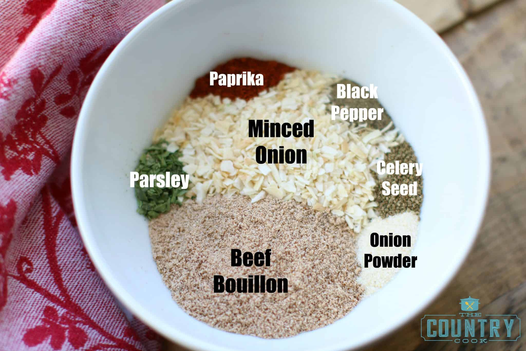 ingredients for onion soup mix in a white bowl with text above each ingredient to identify it.
