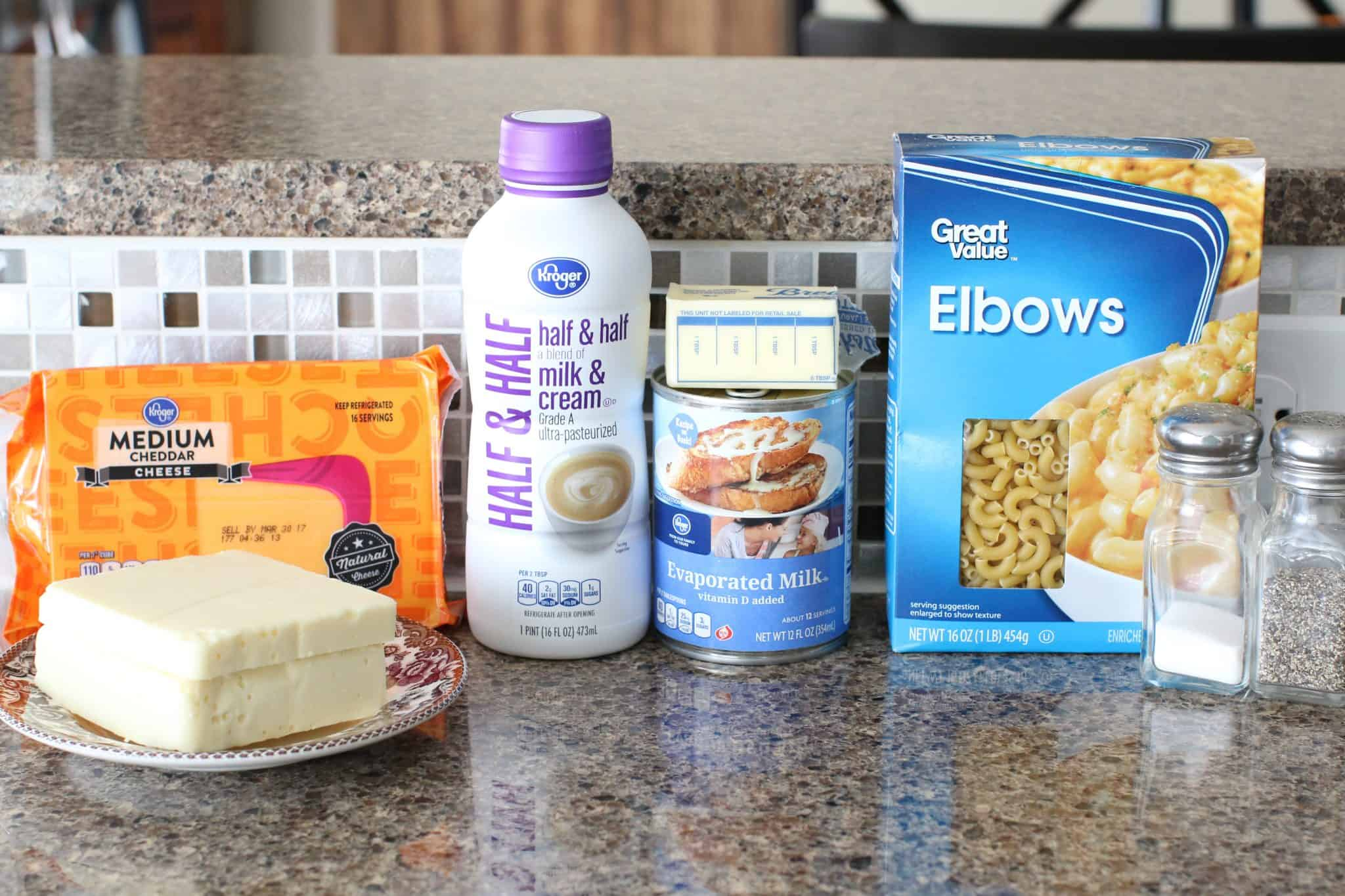 ingredients needed to make slow cooker macaroni and cheese: elbow macaroni, salted butter, evaporated milk, half & half, shredded cheddar cheese, white American cheese, salt and pepper.