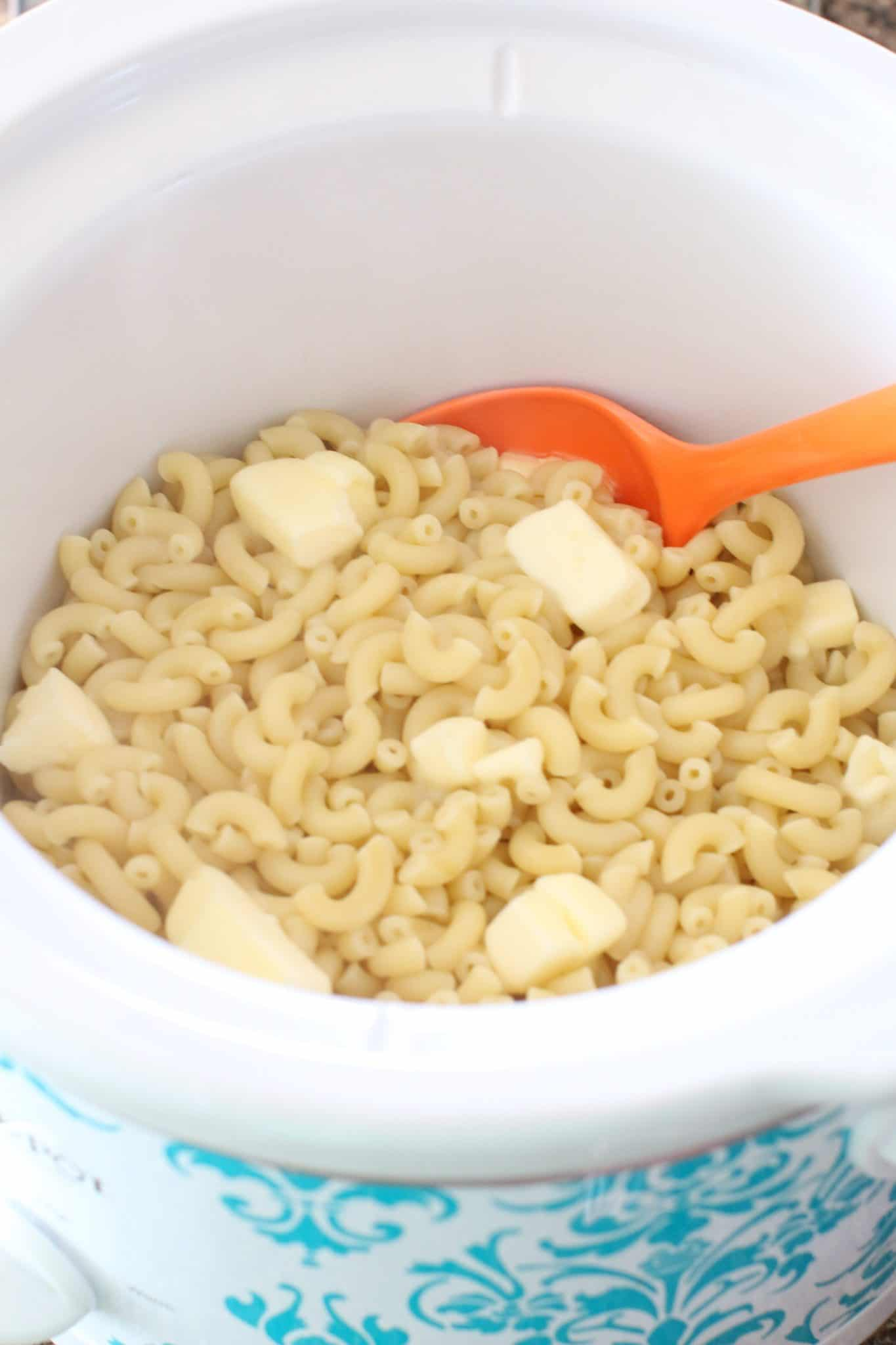 cooked macaroni noodles in a slow cooker with butter on top and a plastic orange spoon inserted into the noodles.