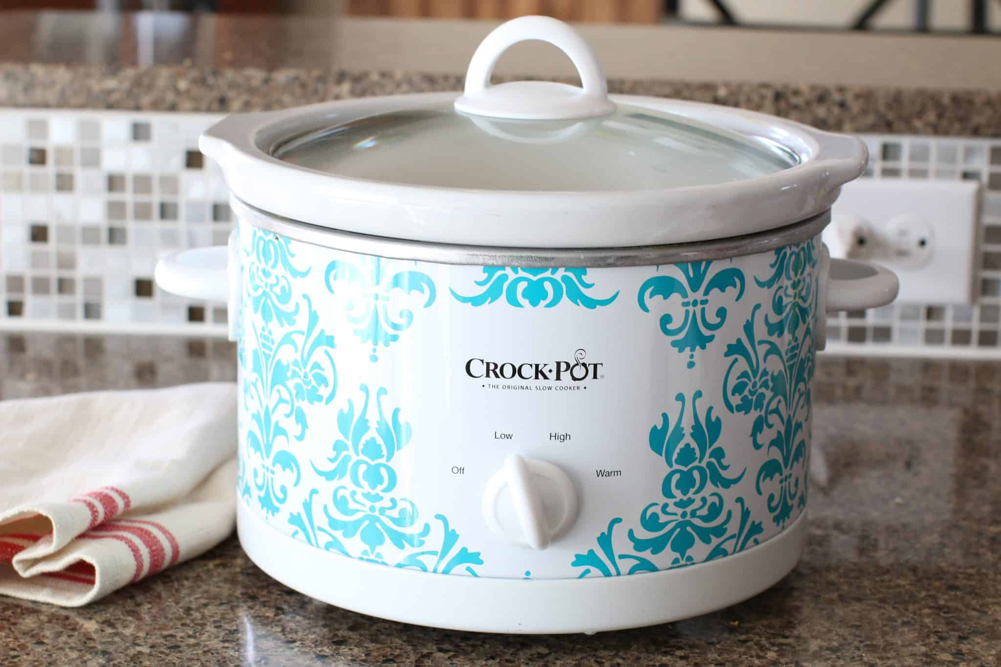 A white and light blue 3.5 quart crock pot with a lid on top.