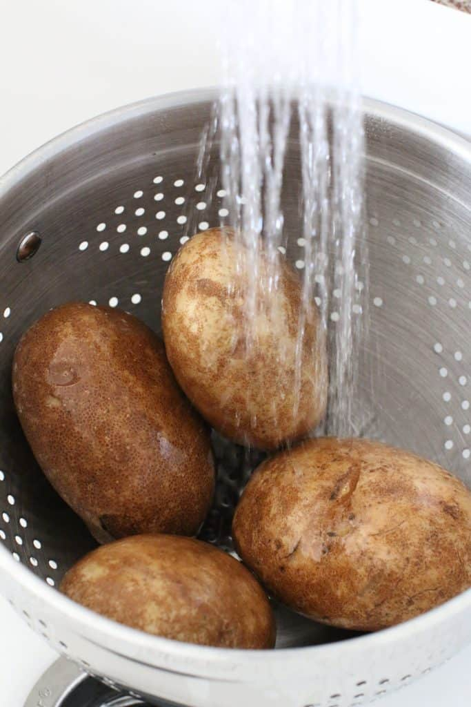 rinsing russet potatoes in a colander