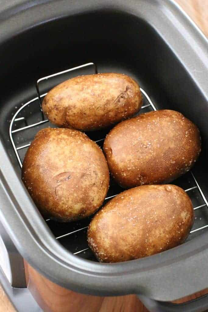 four large russet potatoes in the bottom of a 6-quart crock pot