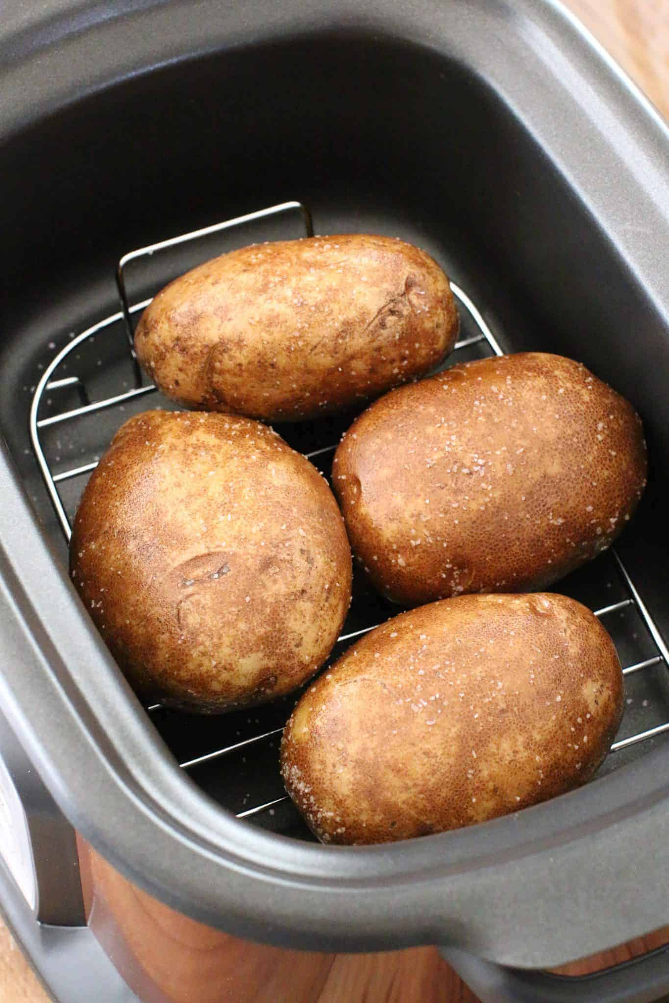 four large russet potatoes in the bottom of a 6-quart oval crock pot.