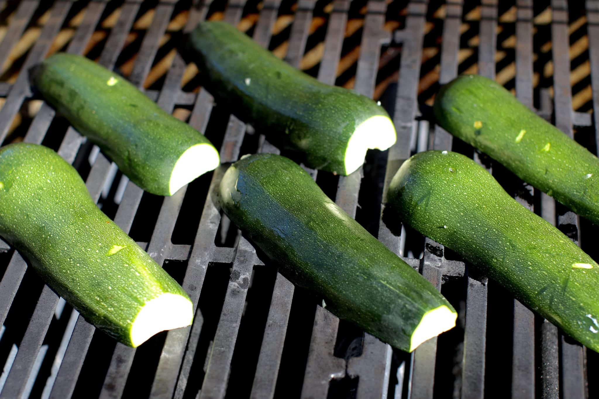 zucchini halves shown cut side don on the grates of a propane grill.