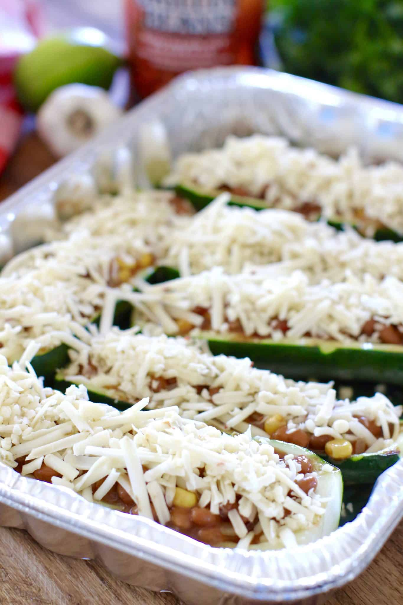 shredded cheese sprinkled on top of zucchini halves.