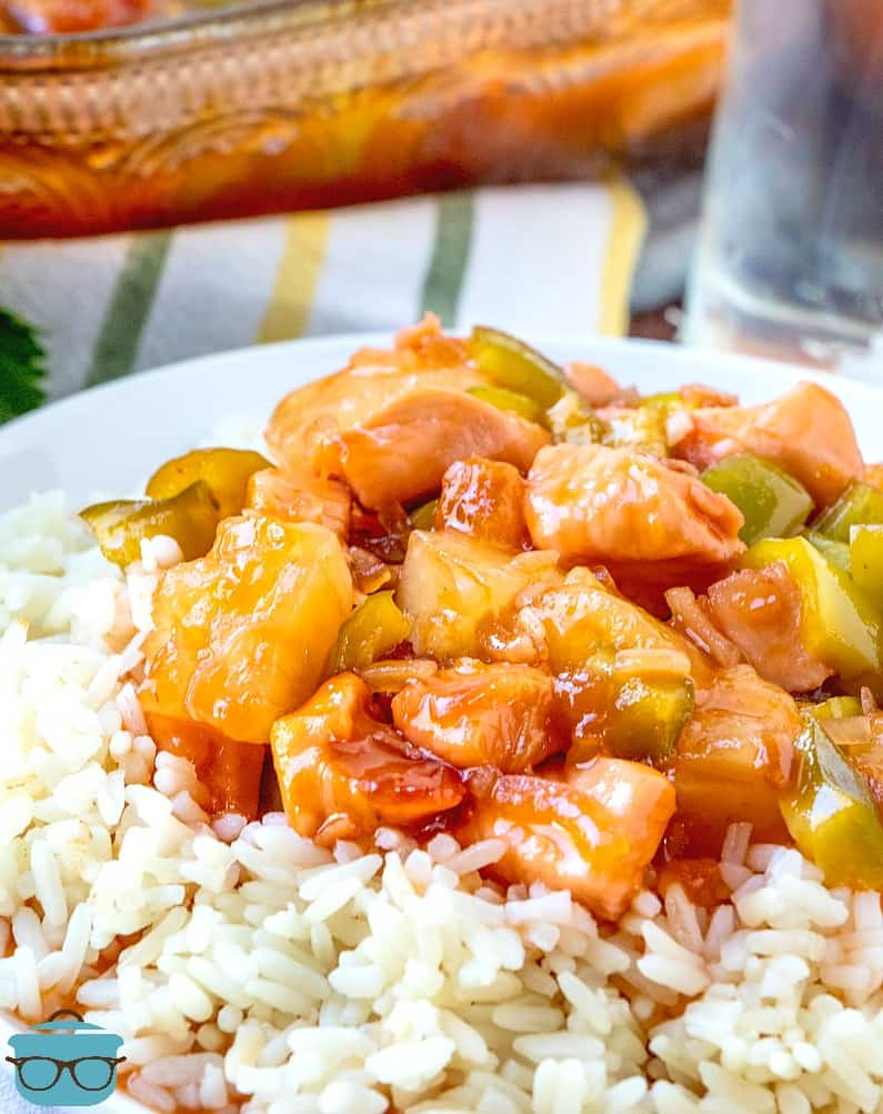 Baked Sweet and Sour Chicken with pineapple and green pepper served over white rice on a white plate with baking dish in the background