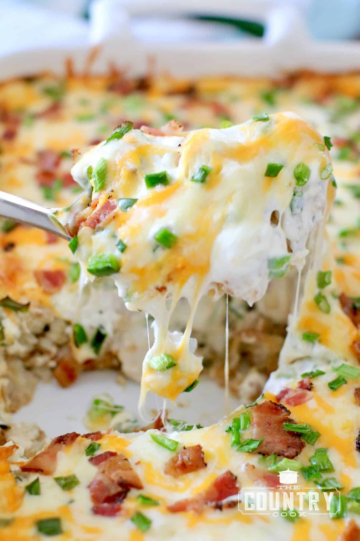 Jalapeno Popper Tater Tot Chicken Casserole shown with a large silver spoon scooping up a serving with melted cheese pulling.
