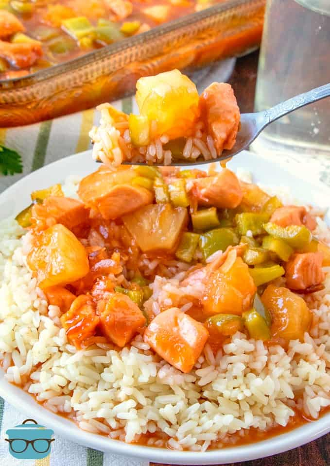 forkful of baked sweet and sour chicken and rice with full seving on a plate underneath fork