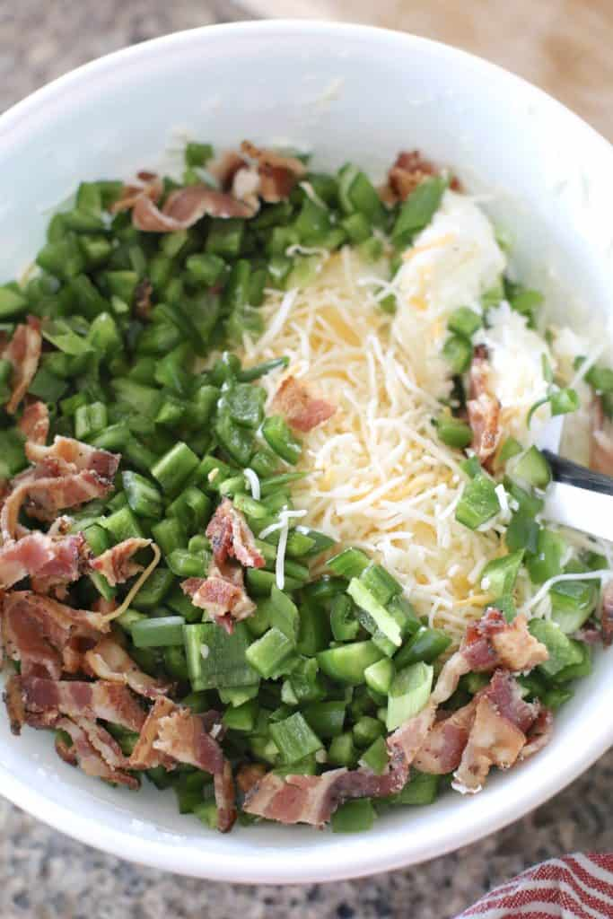 cream cheese, sour cream, bacon and shredded cheese in a bowl