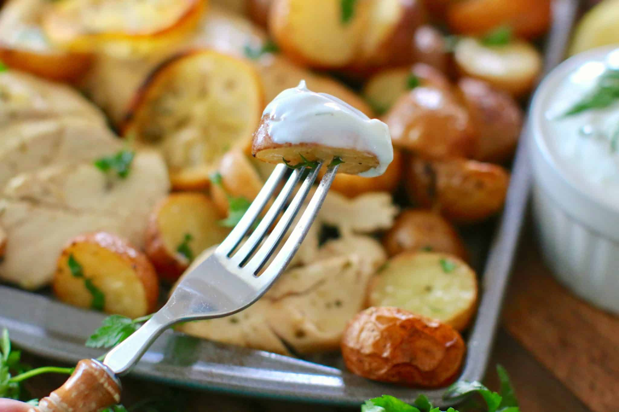 fork holding half of a baked potato that has been dipped in tzaziki sauce.