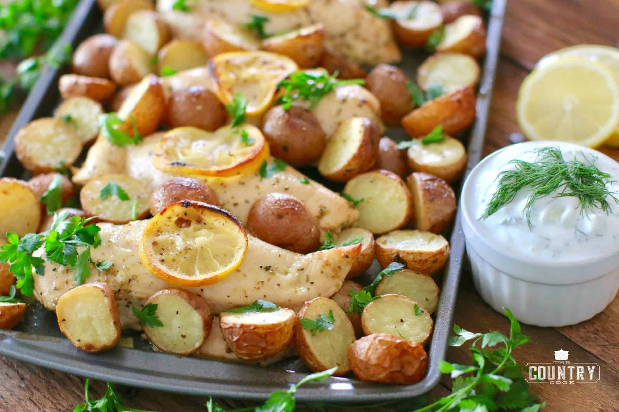 fully cooked chicken and potatoes on baking sheet and topped with fresh parsley.