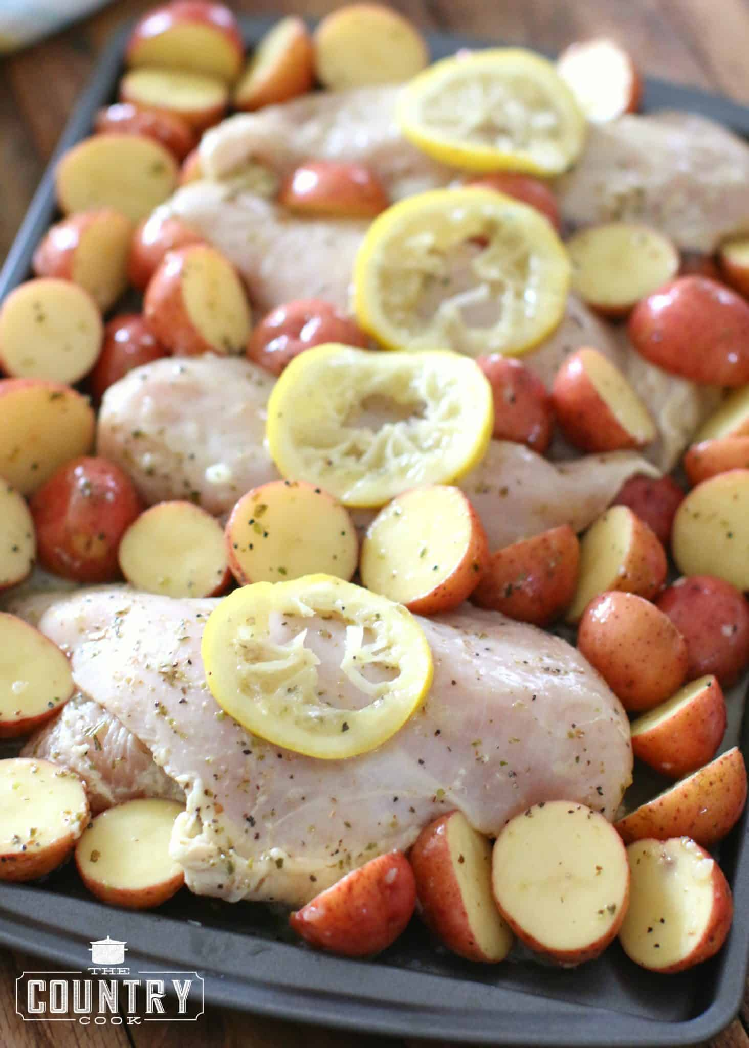 marinated chicken breasts and sliced little potatoes placed evenly on a baking sheet and topped with sliced lemon.