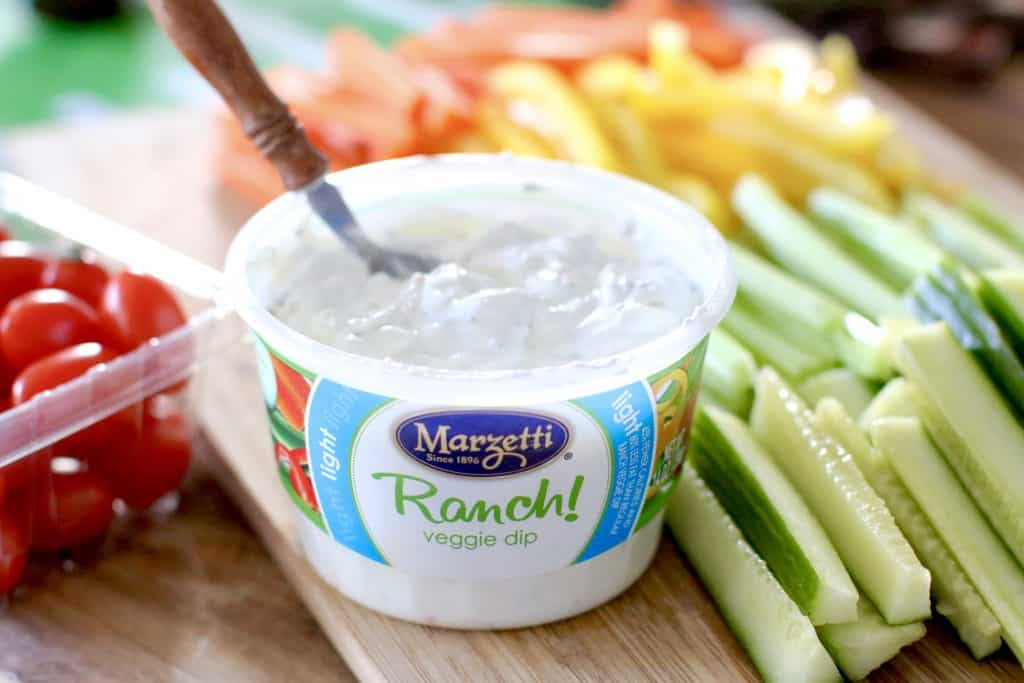an opened tub of Marzetti Ranch Dip with a spoon inside