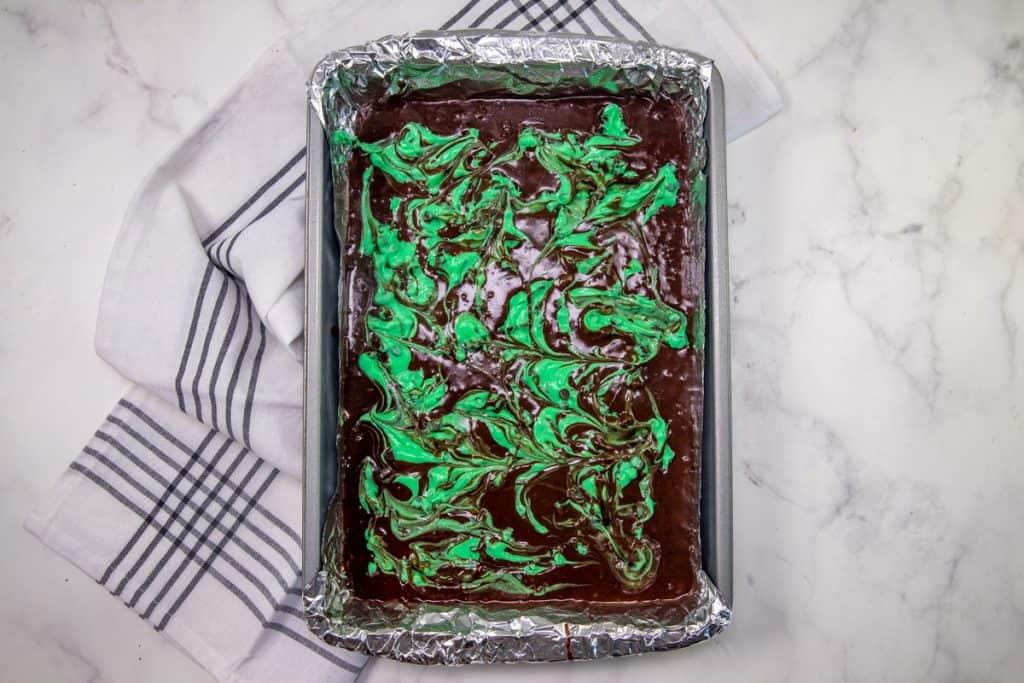green cream cheese shown swirled through brownie batter in baking pan