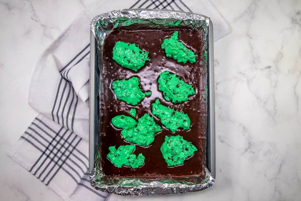 brownie batter in a baking pan with bright green cream cheese dotted on top of the brownie batter