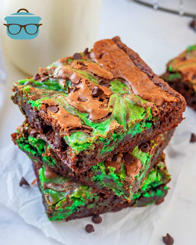 stack of three mint chocolate chip brownies on a parchment paper square