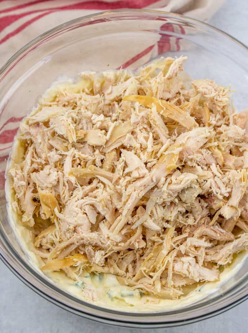 shredded cooked chicken mixed together with sour cream, cream of chicken, sliced green onion mixed together in a bowl.